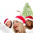 Group of three happy pretty girls are celebrating christmas and — Stock Photo