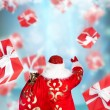 Santa Claus standing and doing magic. Gift boxes falling down ar — Stock Photo #12718782