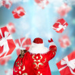 Santa Claus standing and doing magic. Gift boxes falling down ar — Stock Photo