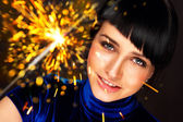 Portrait of young attractive celebrating woman holding sparkles — Stock Photo