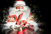 Santa Claus holding his bag and smiling. Lights and sparks are f — Stock Photo