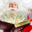 Santa sitting at the Christmas tree, fireplace and reading a boo — Stock Photo #13177824