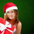 Young happy girl in Christmas hat. Holding huge christmas gift — Stock Photo