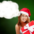 Young happy girl in Christmas hat. Holding huge christmas gift. — Stock Photo #13177846