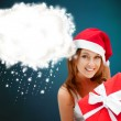 Young happy girl in Christmas hat. Holding huge christmas gift. — Stock Photo #13177849