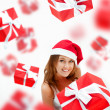 Young woman holding gift box wearing santa claus hat. Many gift — Stock Photo #13177862