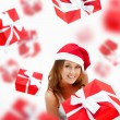 Young woman holding gift box wearing santa claus hat. Many gift — Stock Photo