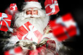 Santa Claus holding his bag and smiling. Gift boxes are flying f — Stock Photo