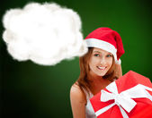 Young happy girl in Christmas hat. Holding huge christmas gift. — Stock Photo