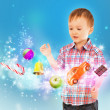 Little boy conjuring toys and confection with his hands — Stock Photo #13251123