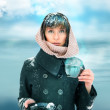 Young woman standing with cup of coffee or tea. Snow on her head — Stock Photo #13251150