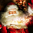 Santa Claus at home at night making magic - Stock Photo