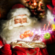 Santa Claus getting gifts and confection from his bag and showin — Stock Photo #13251207
