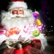 Santa Claus getting gifts and confection from his bag and showin — Stock Photo #13251238
