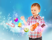 Little boy conjuring toys and confection with his hands — Stock Photo