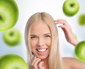 A beautiful slender girl smiling with green apples falling aroun — Stock Photo