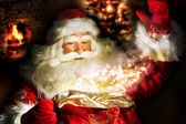 Santa Claus at home at night making magic — Stok fotoğraf