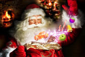 Santa Claus getting gifts and confection from his bag and showin — Stok fotoğraf