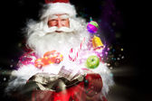 Santa Claus getting gifts and confection from his bag and showin — 图库照片