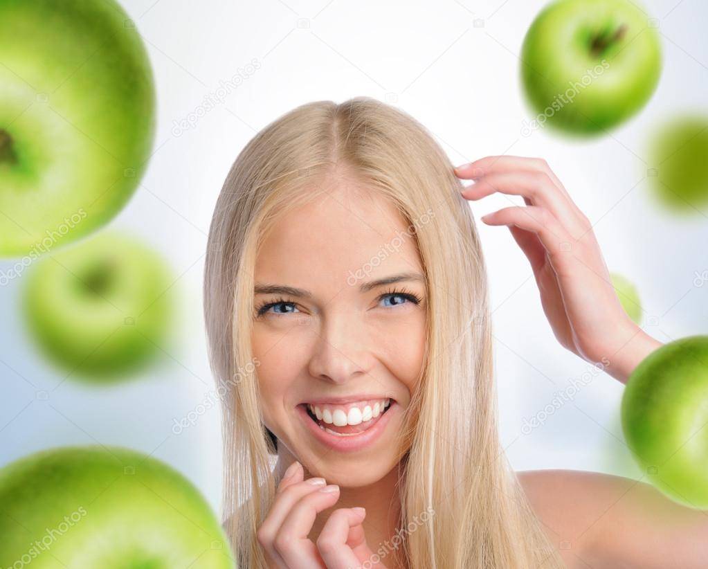 A beautiful slender girl smiling with green apples falling around her  Stock Photo #13251143