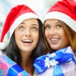 Young happy girls in Christmas hats. Standing together indoors a — Stock Photo #13623072