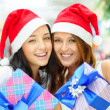 Young happy girls in Christmas hats. Standing together indoors — Stock Photo