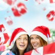 Young happy girls in Christmas hats. Standing together indoors — Stock Photo #13623244