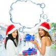Young happy girls in Christmas hats.Standing together indoors, — Foto de Stock
