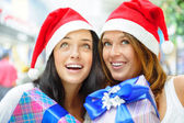 Young happy girls in Christmas hats. Standing together indoors a — Stock Photo