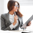 Beautiful business woman looking at papers she holding in her ar — Stock Photo #13856737