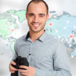 Adult man holding binoculars against world map. Looking for professional office staff — Stock Photo #13856762