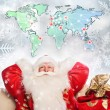 Santa Claus preparing for Christmas. He is using digital worldma — Stock Photo