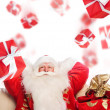 Santa Claus sitting with a sack indoor relaxing and Gift boxes f — Stock Photo