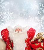 Weihnachtsmann sitzend mit einem sack indoor auf silwer snowfl — Stockfoto
