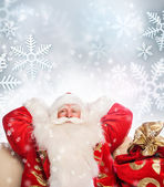 Santa Claus sitting with a sack indoor relaxing on silwer snowfl — Stock Photo