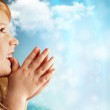 Portrait of young smiling praying girl in blue dress against sky — Stock Photo