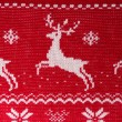 Real red knitted background with white Christmas deers and snowf - Stock Photo