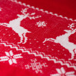 Real red knitted background with white Christmas deers and snowf - Стоковая фотография