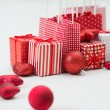 Gift boxes with xmas presents wrapped in red paper with ornament — Stock Photo