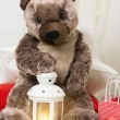 Christmas teddy bear sitting with lantern and gifts around - Stock Photo