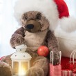 Christmas teddy bear wearing a santa hat sitting with lantern an — Stock Photo #14604117