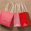 Red gift package paper bags hanging on a ribbon. Old brown paper — Stock Photo #14605673