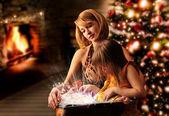 Jovem mãe e filha lendo livrinho dela sentada a — Foto Stock