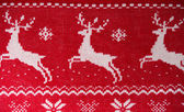 Real red knitted background with white Christmas deers and snowf — Stock Photo