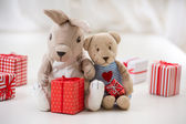Retro style toy rabbit and bear sit hugging with gift boxes — Stock Photo