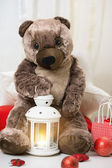 Christmas teddy bear sitting with lantern and gifts around — Stock Photo