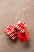 Red gift boxes hanging on a ribbon. Old brown paper background — Stock Photo