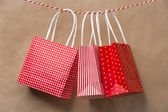 Red gift package paper bags hanging on a ribbon. Old brown paper — Stock Photo