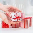 Female hands holding a little gift near red Gift boxes - shoppin — Stock Photo #14975885