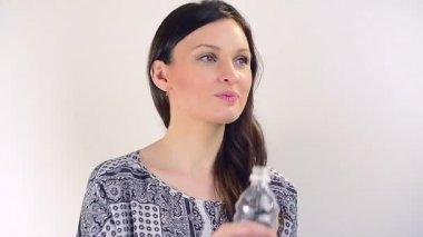Vacker flicka dricksvatten från blå flaska — Stockvideo